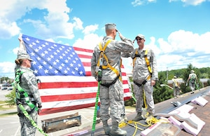Tech. Sgt. Scott Fillar, right, salutes 1st Lt. Pete Moran on an under-construction roof Aug. 1, 2015 at the Pittsburgh International Airport Air Reserve Station, Pa. Fillar, a heating ventilation air conditioning and refrigeration foreman with the 911th Civil Engineer Squadron, reenlisted for three years. (U.S. Air Force photo by Staff Sgt. Justyne Obeldobel)