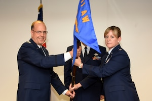 Lt. Col. Jennifer Fitch, commander of the 911th Operations Support Squadron, accepts the guideon from 911th Operations Group Commander Col. Jeff Potts at the Pittsburgh International Airport Air Reserve Station, August 1, 2015. Fitch, who was stationed in locations like Japan and South Carolina, assumed command of the 911th OSS over the August unit training assembly. (U.S. Air Force photo by Senior Airman Marjorie A. Bowlden)