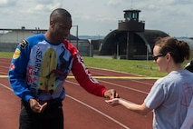 U.S. Air Force Senior Airman Darrius Willingham, a 52nd Communications Squadron postal clerk, hands a bead to a participant during the Relay for Life event at the outdoor track on Spangdahlem Air Base, Germany, July 31, 2015. Willingham and other volunteers handed a bead to each participant every time they completed a lap to keep track of how many they did. More than 30 volunteers supported the event. (U.S. Air Force photo by Airman 1st Class Luke Kitterman/Released)