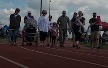Select participants take the first lap to start the Relay for Life event at the outdoor track on Spangdahlem Air Base, Germany, July 31, 2015. The first lap, also known as the survivors' lap, features all cancer survivors at the event being cheered on by other participants lined around the track, celebrating the survivors' victory over cancer. (U.S. Air Force photo by Airman 1st Class Luke Kitterman/Released)
