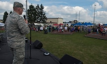 U.S. Air Force Col. Joe McFall, 52nd Fighter Wing commander, gives an opening speech before the start of the Relay for Life event at the outdoor track on Spangdahlem Air Base, Germany, July 31, 2015. More than 200 people participated in the 12-hour event which consisted of different themed music and costumes each hour. (U.S. Air Force photo by Airman 1st Class Luke Kitterman/Released)