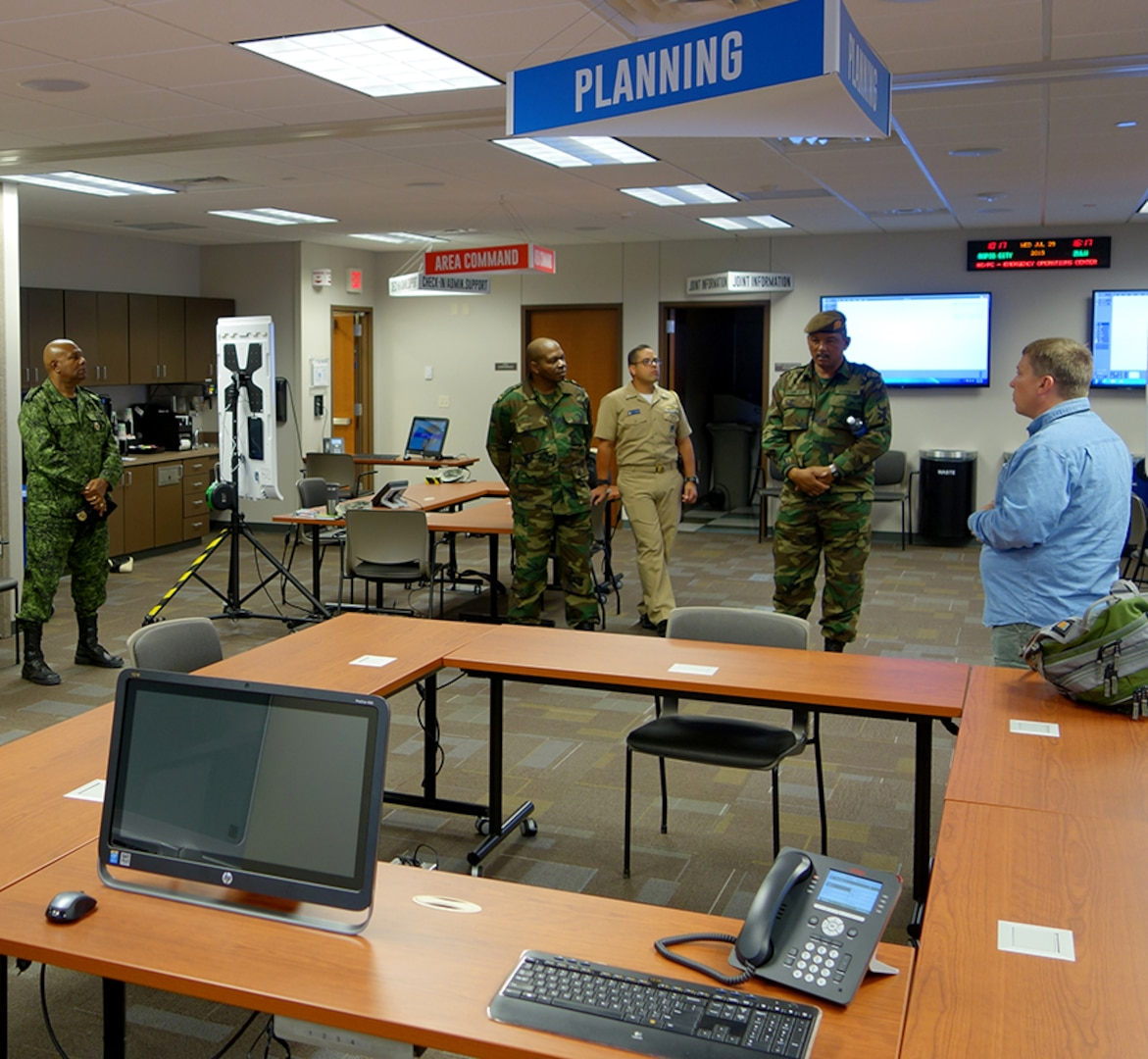 Members of Suriname's Defense discuss emergency operations with an official from the Pennington County emergency management office in Rapid City, S.D., July 28, 2015. The Surinamese service members were in South Dakota on a subject matter expert exchange focusing on emergency operations through the National Guard Bureau's State Partnership Program.