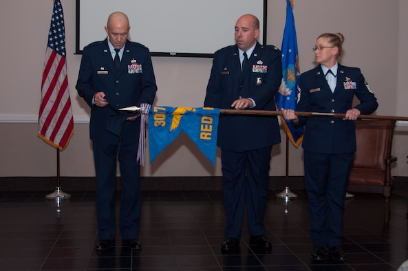 U. S. Air Force Colonel Timothy Lamb, commander of the 622th Civil Engineer Group, Dobbins Air Force Base, Georgia, and Lt. Col. Charles Chapman, 307th RED HORSE commander, furl and prepare to encase the unit's flag at Barksdale Air Force Base, Louisiana., Aug. 2, 2015. During the inactivation ceremony, the furling and encasing of the organization's flag, signifies the unit has completed its mission. The 307th RH was inactivated after 44 years of service making it the longest continuously operational RED HORSE squadron in the Air Force. (U.S. Air Force photo by Master Sgt. Laura Siebert)