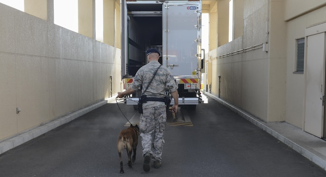 Staff Sgt. Nicholas Galbraith, a 374th Security Forces Squadron military working dog handler, and Topa, a 374 SFS MWD, perform security checks at Yokota Air Base, Japan, July 24, 2015. Topa is Galbraith's first canine partner outside of training, and they have been working together for one year. (U.S. Air Force photo/Airman 1st Class David C. Danford)