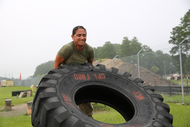Staff Sgt. Marissa Grudowski executes a tire flip aboard Marine Corps Air Station Beaufort, Aug, 4, to prepare for the Ultimate Tactical Athlete competition. The competition is scheduled for Sept. 16 at Marine Corps Air Ground Combat Center Twentynine Palms, Calif. Grudowski is a mobile facilities technician with Marine Aviation Logistics Squadron 31, Marine Aircraft Group 31. (U.S. Marine Corps photo by Lance Cpl. Jonah Lovy/released)