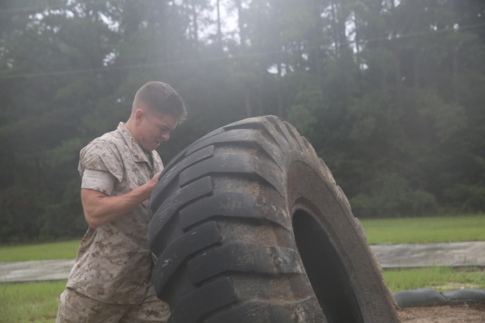 Lance Cpl. Brandon Gitz executes a tire flip aboard Marine Corps Air Station Beaufort, Aug, 4, to prepare for the Ultimate Tactical Athlete competition. As the top scoring Male competitor, Gitz is invited to compete in the next round at Marine Corps Air Ground Combat Center Twentynine Palms, Calif. Gitz is a cryogenics equipment operator with Marine Aviation Logisitics Squadron 31, Marine Aircraft Group 31.. (U.S. Marine Corps photo by Lance Cpl. Jonah Lovy/released)