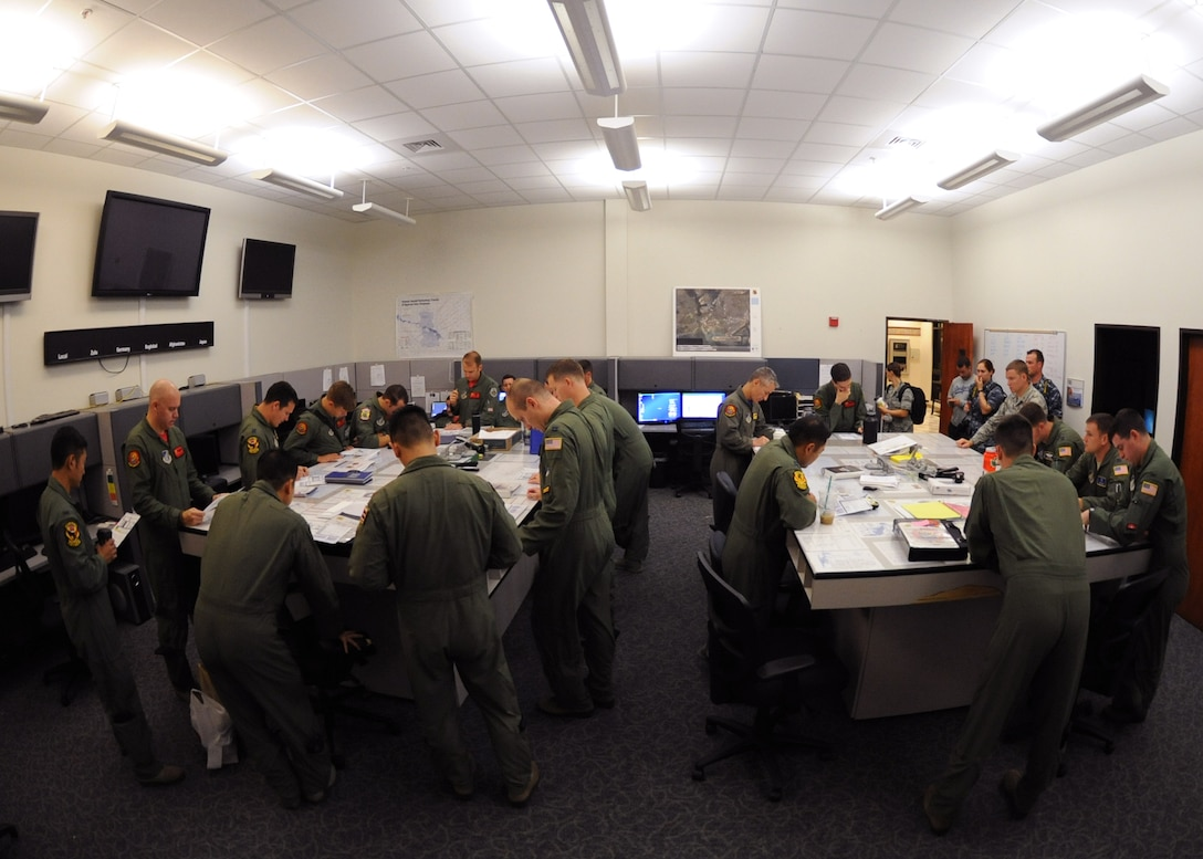 U.S. Air Force aircrew from the 535th Airlift Squadron conduct a pre-mission briefing on Joint Base Pearl Harbor-Hickam, Hawaii, July 31, 2015. Active duty and Air National Guard Airmen joined forces in a Warrior Day to demonstrate the cooperation and capabilities of total force integration. During the Warrior Day training, five C-17 Globemasters III simulated combat maneuvers in a hostile environment, airdrops, and refueling operations. (U.S. Air Force photo by Tech. Sgt. Aaron Oelrich/Released)