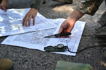 Staff Sgt. Zachariah Angel (right), Survival, Evasion, Resistance and Escape (SERE) operations craftsman with the 910th Operations Support Squadron, points out coordinates on a map of Camp Ravenna here, July 31, 2015. Maj. Vince Repucci (left), a pilot with the 757th Airlift Squadron, studies the map. Approximately ten aircrew members were at Camp Ravenna Joint Military Training Center for an aircrew combat survival skills training course. The course is a triennial requirement for aircrew members and provides skills for surviving, evading capture, resisting the enemy and escaping a hostile environment. (U.S. Air Force photo/Eric M. White)
