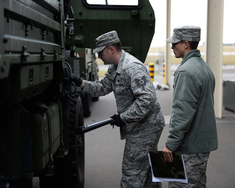 Two U.S. Air Force Airmen from the 606th Air Control Squadron perform a pre-departure inspection on a five-ton truck during mobile deployment training July 31, 2015, at Spangdahlem Air Base, Germany.  The inspection represents the final task Airmen must accomplish before departing on a training convoy. (U.S. Air Force photo by Senior Airman Dylan Nuckolls/Released)