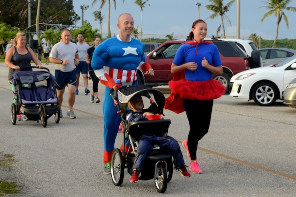 Airmen and family members participate in a Superhero Scramble 5K run Aug. 5, 2015, at Andersen Air Force Base, Guam. Some participants donned their superhero outfits while others wore their favorite superhero T-shirt. (U.S. Air Force photo by Airman 1st Class Alexa Ann Henderson/Released)