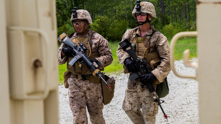 Corporal Eduardo Tovar (left) and Lance Cpl. Tim Kerschner (right), military policemen with Bravo Company, 2nd Law Enforcement Battalion, II Marine Expeditionary Force Headquarters Group, patrol around GSRA FOB, looking for possible intruders aboard Camp Lejeune, North Carolina, August 5, 2015. The company conducted a week long exercise, from August 4-7, in preparation for an upcoming deployment, where they will have to take on the roles of security forces and protect valuable assets.