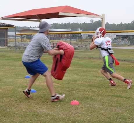 Adam Crosby, special teams' coordinator quarterback and receiver coach, Sherwood Christian Academy, Albany, Ga., recently practices with a student during a weeklong training camp held at Marine Corps Logistics Base Albany.