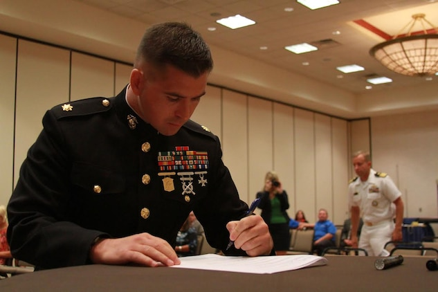 U.S. Marine Corps Maj. Gabriel L. Diana, commanding Officer of Recruiting Station Charleston, West Virginia., and a native of Columbus, Ohio, signs the Common Ground Compact July 29, 2015, at the Waterfront Convention Center in Morgantown, West Virginia.  The compact is a combined effort between the Department of Education and the military to reduce the high school dropout rate and ensure students across West Virginia are career and college ready. (U.S. Marine Corps photo by Sgt. Caitlin Brink/Released)