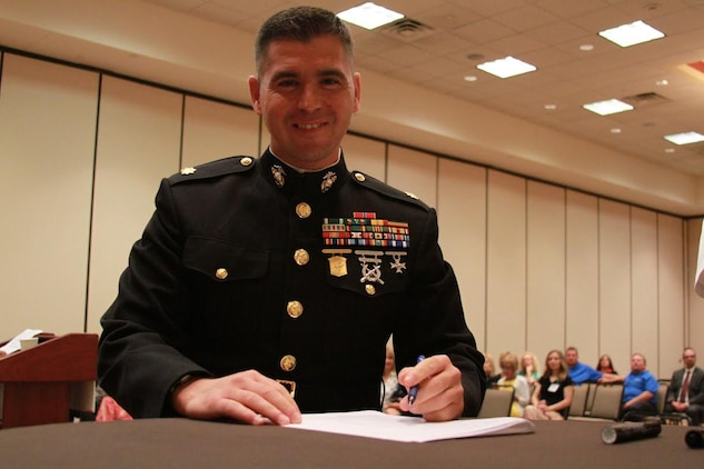 U.S. Marine Corps Maj. Gabriel L. Diana, Commanding Officer of Recruiting Station Charleston, West Virginia., and a native of Columbus, Ohio, poses after signing the Common Ground Compact July 29, 2015, at the Waterfront Convention Center in Morgantown, West Virginia.  The compact is a combined effort between the Department of Education and the military to reduce the high school dropout rate and ensure students across West Virginia are career and college ready. (U.S. Marine Corps photo by Sgt. Caitlin Brink/Released)