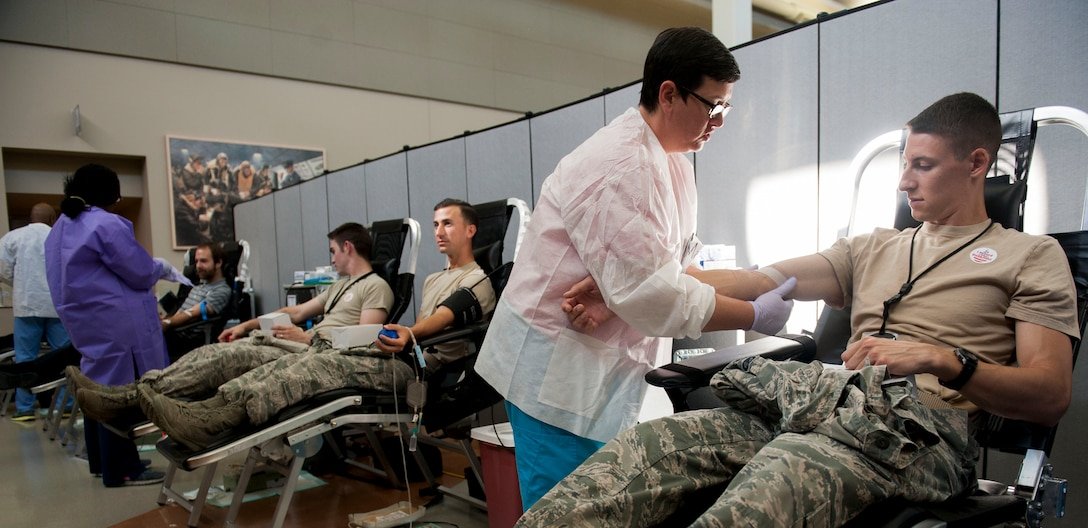 Members from the National Air and Space Intelligence Center give blood during the bi-annual blood drive Tuesday, July28, 2015. There are about 30,000 units of blood used every day in the United States. (U.S. Air Force photos by Airman 1st Class Samuel Earick)