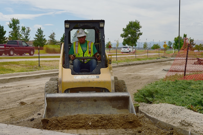 Orrin Devenport, Rocky Mountain Excavating operator, uses a skid steer loader during construction of the new Copper Mountain parking lot Aug. 6, 2015, on Buckley Air Force Base, Colo. The project, which began in June, is renovating the roadways on Buckley. It will include improvements to Eldora Street, Camp Hale Way and Telluride Street, and is expected to be completed in September. (U.S. Air Force photo by Airman 1st Class Luke W. Nowakowski/Released)