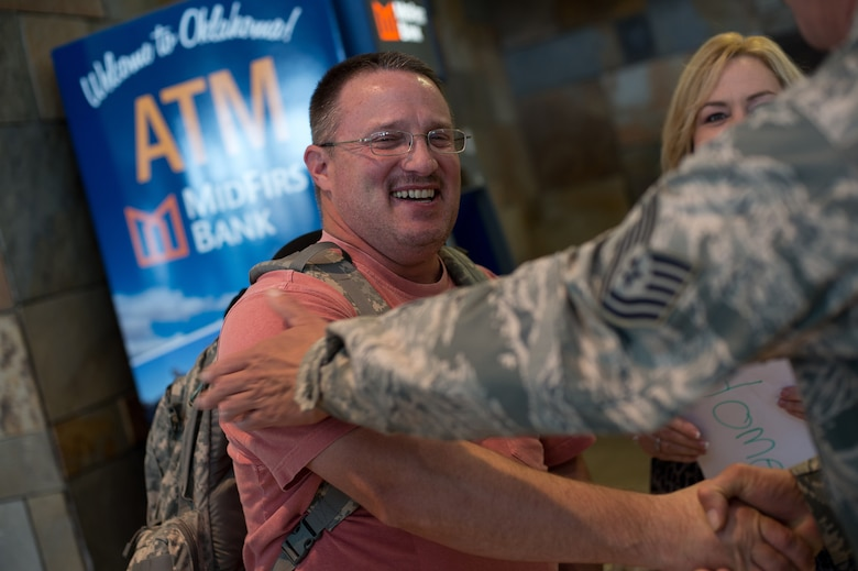 Senior Master Sgt. Jeffrey Woodall, 205th Engineering Installation Squadron unit project manager, reunites with his family at Will Rogers World Airport, Aug. 2, 2015, after returning from a six-month deployment to Southwest Asia. The 205 EIS was providing support for the enhancement of their Command and Control, Communications, Computers, Intelligence, Surveillance and Reconnaissance (C4ISR) capabilities. (Air National Guard photo by Senior Airman Tyler K. Woodward/Released)