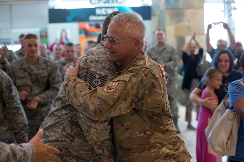 Master Sgt. Bryan Robinson, 205th Engineer Installation Squadron quality assurance NCO in charge, reunites with his family at Will Rogers World Airport, Aug. 2, 2015, after returning from a six-month deployment to Southwest Asia. The 205 EIS was providing support for the enhancement of their Command and Control, Communications, Computers, Intelligence, Surveillance and Reconnaissance (C4ISR) capabilities. (Air National Guard photo by Senior Airman Tyler K. Woodward/Released)