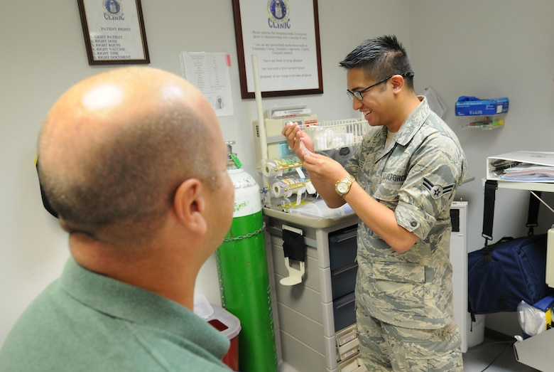 U.S. Air Force Airman 1st Class William Sales, an aerospace medical technician from the New Jersey Air National Guard's 177th Medical Group, demonstrates proper immunization techniques at the 86th Medical Clinic on Ramstein Air Base, Germany, Aug. 6. Sales is in the process of completing his immunization back-up technician training at the clinic. (U.S. Air National Guard photo by Senior Airman Shane S. Karp/Released)