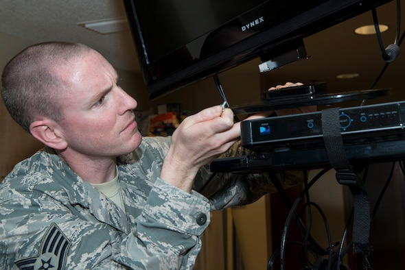 U.S. Air Force Staff Sgt. Nathan Hawley, 23d Civil Engineer Squadron airman dormitory leader, fixes a television during a maintenance check Aug. 5, 2015, at Moody Air Force Base, Ga. ADLs conduct individual monthly maintenance checks on all 13 dormitory facilities to sustain great quality of life for Airmen in the dorms. (U.S. Air Force photo by Airman 1st Class Kathleen D. Bryant/ Released)