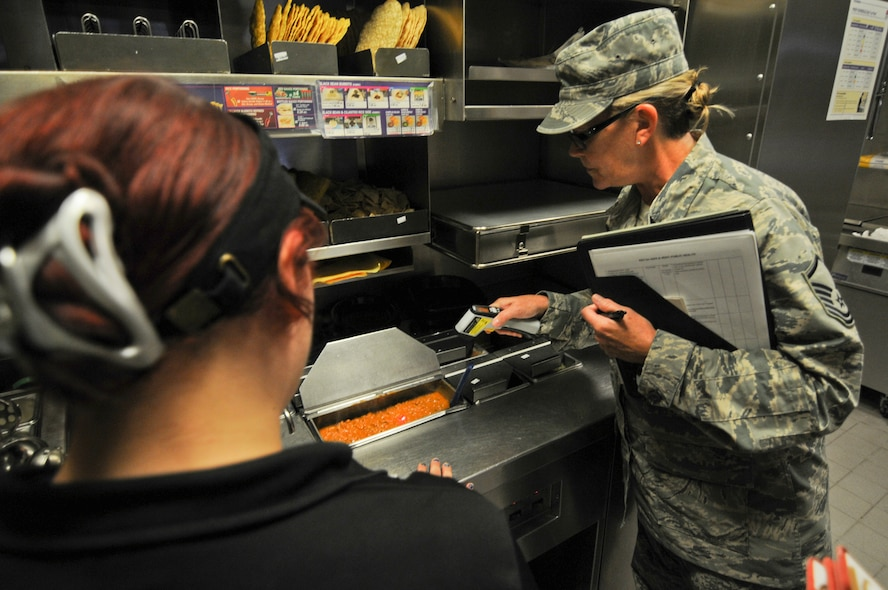 U.S. Air Force Master Sgt. Patricia Hughes, a public health technician with the New Jersey Air National Guard's 177th Medical Group, ensures meat is of the proper temperature during an inspection at one of the restaurants on Spangdahlem Air Base, Germany, Aug. 4. Restaurants on base are inspected about once per month to ensure the facilities are operating properly. (U.S. Air National Guard photo by Senior Airman Shane S. Karp/Released)