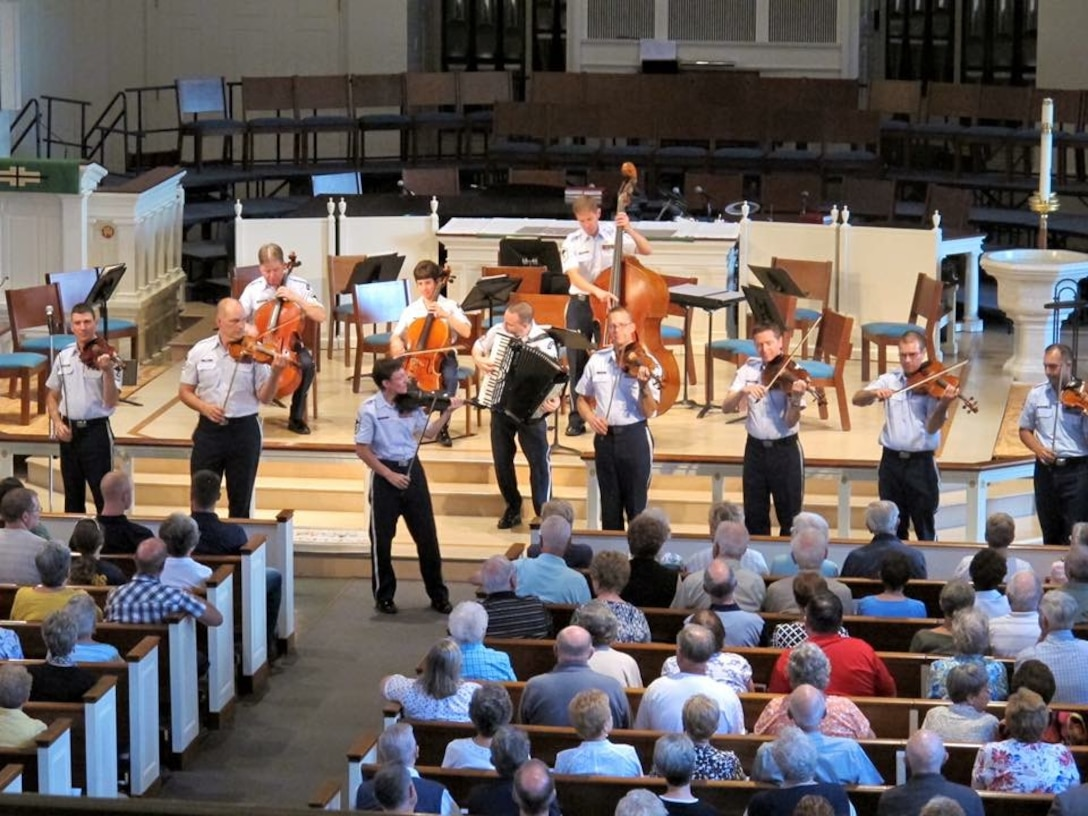 Chief Master Sergeant Deb Volker leads the Air Force Strings in a strolling show at Trinity Lutheran Church in Lansdale, Pennsylvania.  The concert was part of their 7-day community relations tour of the Northeast. (U.S. Air Force Photo/released)