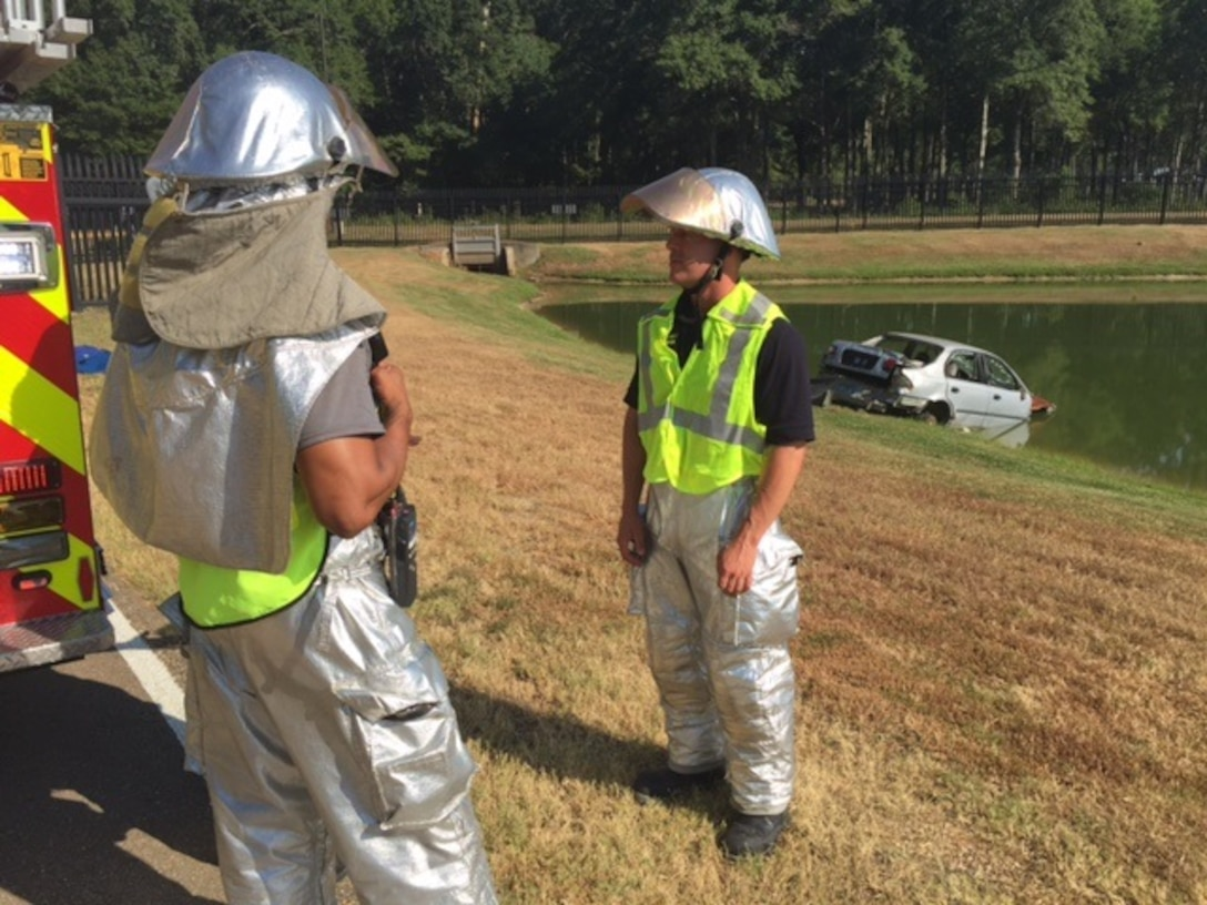 Members of the 172d Airlift Wing's Fire Department Engine No. 6 crash team discuss strategy during the incident command response exercise. An incident command response exercise for the 172d Airlift Wing took place on August 4, 2015. The 172d AW Security Forces immediately responded to the exercise scenario that involved a vehicle losing control at the main gate. The out of control vehicle splashed into the pond and a passenger was trapped. Security Forces alerted the base fire department and crash teams arrived to carry out rescue operations as an incident command post was established.