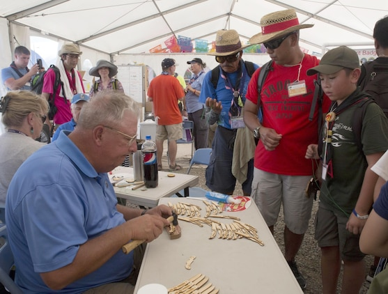 Mikah Ricafrente, a Boy Scout with Troop 77, and his father, Master Sgt. Nephtali D. Ricafrente, watch as a world scout volunteer assembles wooden knives in the Boy Scouts of America tent at the 23rd World Scout Jamboree in Kirara-hama, Yamaguchi, Japan, August 1, 2015. This is Japan's second time hosting the World Scout Jamboree, which occurs every four years. The U.S., Mexico and Canada are co-hosting the 24th World Scout Jamboree in 2019, in West Virginia.