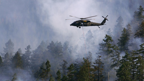 "Oregon Army National Guard pilots, Chief Warrant Officer 4 Dennis Cooper, Chief Warrant Officer 2 Logan Bass, and crew chief Spc. Beth Bechard, with Charlie Company, 7-158th Aviation, navigate through smoke on the way to their drop site in support of firefighting ground crews, Aug. 5, at the Stouts Fire. The Black Hawk helicopter is equipped with a ""Bambi bucket"" which carries approximately 500 gallons of water. Two Oregon Army National Guard HH-60M Black Hawk helicopters have been working out of the Roseburg Municipal Airport since Monday to support ground firefighting crews and have been joined by one Oregon Army National Guard CH-47 Chinook helicopter based out Pendleton, Oregon."