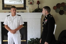 U.S. Marine Corps Capt. Joseph M. Depew, right, former Recruiting Station Cleveland Executive Officer, talks to Midshipman Tomasz Niedzwiecki before awarding him the Naval Reserve Officers Training Corps Scholarship valued at $180,000, June 19, 2015 at Niedzwiecki's home. Niedzwiecki was denied the scholarship on his first attempt during his senior year of high school but improved his application during his freshmen year of college. Niedzwiecki is a midshipman in the NROTC program at Miami University (Ohio) studying mechanical engineering.  (U.S. Marine Corps photo by Sgt. Stephen D. Himes/Released)