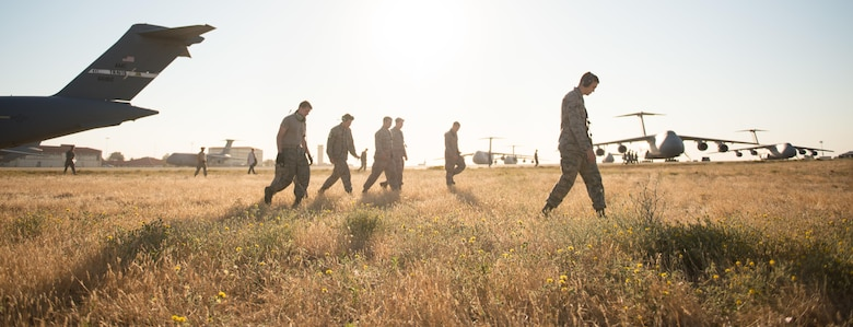 Airmen from the 860th Aircraft Maintenance Squadron at Travis Air Force Base, Calif., perform a foreign object debris walk on the flightline July 29, 2015. Because of the Airmen's efforts to keep the flightline free of FOD, Travis AFB has gone 2,555 days without major damage to an aircraft – helping to ensure mission readiness and lower maintenance costs. (U.S. Air Force photo/Ken Wright)