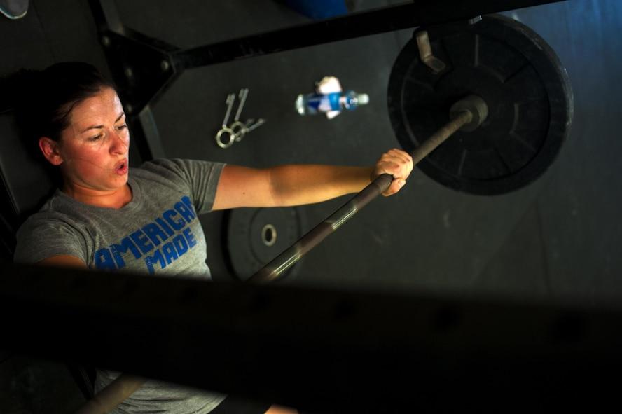 U.S. Air Force Airman 1st Class Sarah M. Bracy, 315th Training Squadron student, performs a bench press at a crossfit gym in San Angelo, Texas, Aug. 6, 2015. Almost diagnosed with diabetes, Bracy started lifting 10 years ago to better her life. (U.S. Air Force photo by Senior Airman Scott Jackson/released)