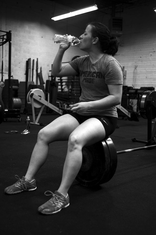 U.S. Air Force Airman 1st Class Sarah M. Bracy, 315th Training Squadron student, rests after lifting at a crossfit gym in San Angelo, Texas, Aug. 6, 2015. Almost diagnosed with diabetes, Bracy started lifting 10 years ago to better her life. (U.S. Air Force photo by Senior Airman Scott Jackson/released)