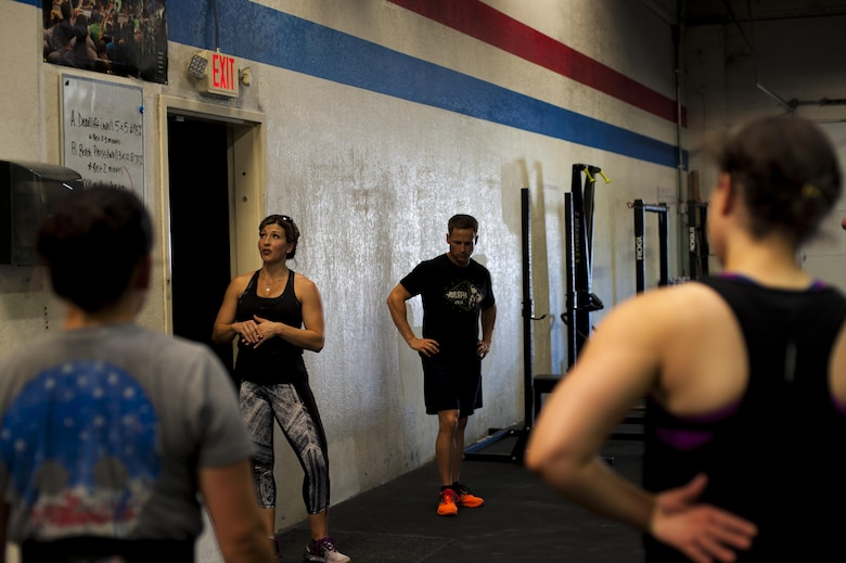 A crossfit coach gives instruction to gym goers at a crossfit gym in San Angelo, Texas, Aug. 6, 2015. Air Force Airman 1st Class Sarah M. Bracy, 315th Training Squadron student, attends the gym after eight hours of class. (U.S. Air Force photo by Senior Airman Scott Jackson/released)