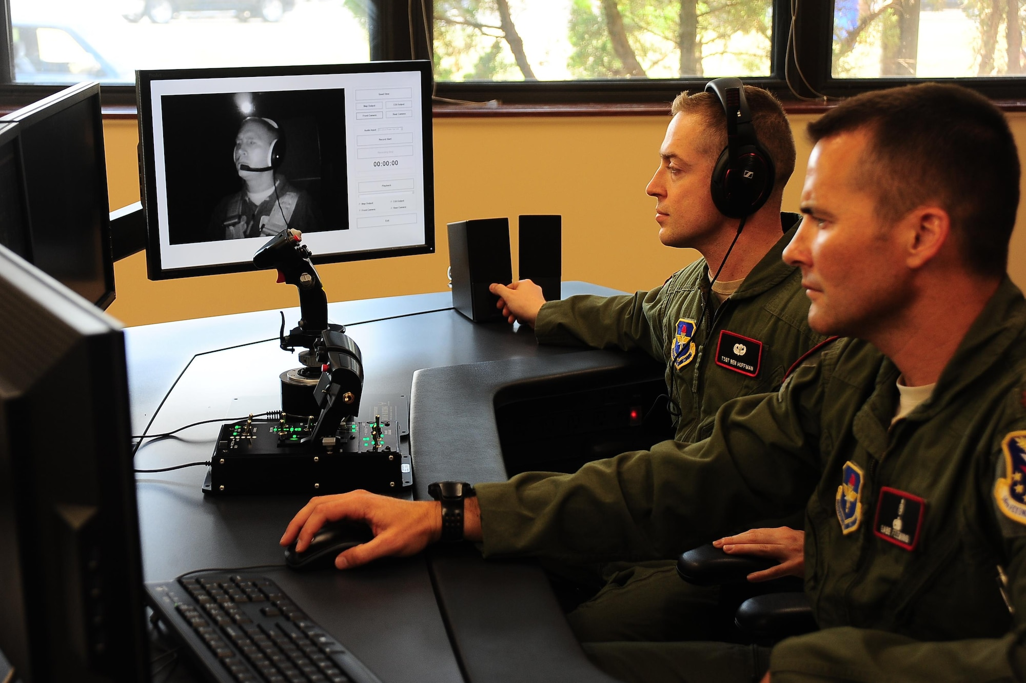 Tech. Sgt. Benjamin Hoffman and Maj. Michael Fleming monitor Col. James Fisher on the video feed from the cockpit of the new spatial disorientation simulator Aug. 5, 2015, at Columbus Air Force Base, Miss. Hoffman and Fleming directed Fisher through various sensations of roll, pitch and yaw to induce spatial disorientation. Hoffman is the 14th Medical Group Aerospace and Operational Physiology Flight chief, Fleming is the 14th MDG AOP Flight commander and Fisher is the14th Flying Training Wing vice commander. (U.S. Air Force photo/Airman 1st Class John Day)