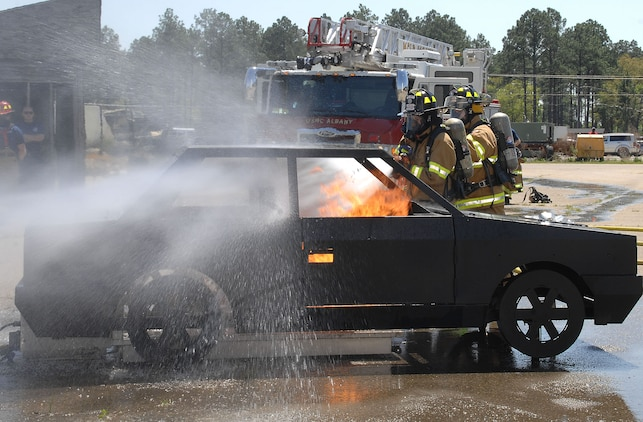 Firefighters Megan Cornell (left) and Tim Wright with Fire and Emergency Services, Marine Corps Logistics Base Albany, attack a controlled vehicle fire during an exercise aboard MCLB Albany, recently. Cornell is the recipient of MCLB Albany's Firefighter of the Year Award for 2015; Public Safety Division Civilian Employee of the Year for 2015 and the Marine Corps Firefighter of the Year Award for 2015.