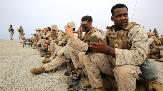 Marines with 3rd Battalion, 5th Marine Regiment, 1st Marine Division, apply camouflage paint before conducting a helicopter raid, as part of the Marine Corps Combat Readiness Evaluation (MCCRE), aboard Marine Corps Base Camp Pendleton, California, Aug. 4, 2015. The MCCRE is used evaluate the operational readiness of a designated unit.