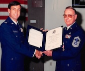 Chief Master Sgt. John Malone, right, retires after serving 26 years on active duty at a ceremony held on Nellis Air Force Base, Nev., in 1990. Malone served a combined 52 years on active duty and in civilian service. (Courtesy photo)