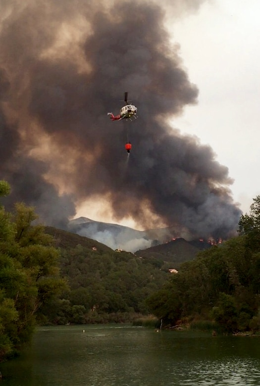 A helicopter transports water from a lake to help extinguish The Rocky Wildfire near Clearlake, California, July 31, 2015. (Courtesy photo)
