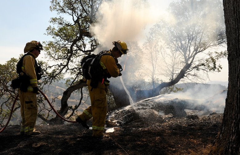 Will Hock (left), 9th Civil Engineer Squadron fire captain, assists Justin Devorss, Linda Fire Protection District engineer, with extinguishing a fire, Aug. 6, 2015, near Clearlake, California. The fire is associated with the Rocky Wildfire that has consumed nearly 70,000 acres in Northern California. (U.S. Air Force Photo by Airman Preston L. Cherry)