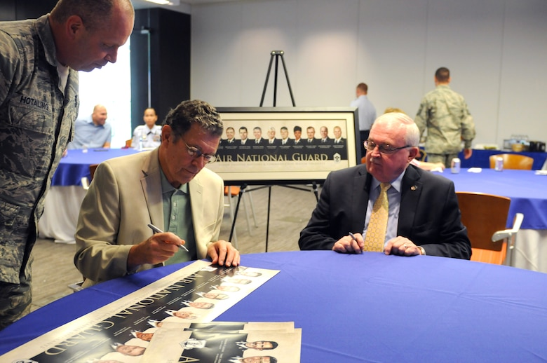Retired Chief Master Sgt. Lynn E. Alexander, former Senior Enlisted Leader to the director of the Air National Guard, center, signs the formers heritage painting lithograph as Chief Master Sgt. James W. Hotaling, command chief master sergeant of the Air National Guard and retired Chief Master Sgt. Richard Smith, former command chief master sergeant of the Air National Guard observe. The lithograph was released as part of the ANG's Focus on the Force week, which gathers senior enlisted leadership to highlight the importance of professional development at all levels, receive feedback from junior enlisted Airmen, and tell the exceptional stories of ANG Airmen throughout the 50 states, territories, and the District of Columbia. (U.S. Air National Guard photo by Master Sgt. David Eichaker/released)