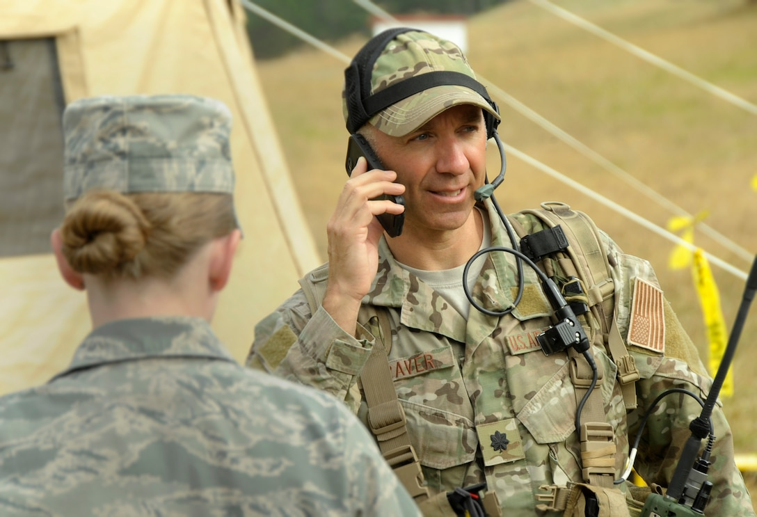 Lt. Col. John Graver, commander of the 304th Rescue Squadron in Portland, Ore., uses a cell phone and other communication equipment to help relay instructions to first responders and other participants taking part in the Pathfinder-Minutemen Exercise, Aug. 5, 2015 at Camp Rilea in Warrenton, Ore. The event is a joint multi-agency, multi-state disaster preparedness exercise based on response to a possible Cascadia Subduction Zone event. Officials believe the Northwest is overdue for a magnitude 7.0 or greater earthquake. (U.S. Air National Guard photo by Tech. Sgt. John Hughel, 142nd Fighter Wing Public Affairs/Released)