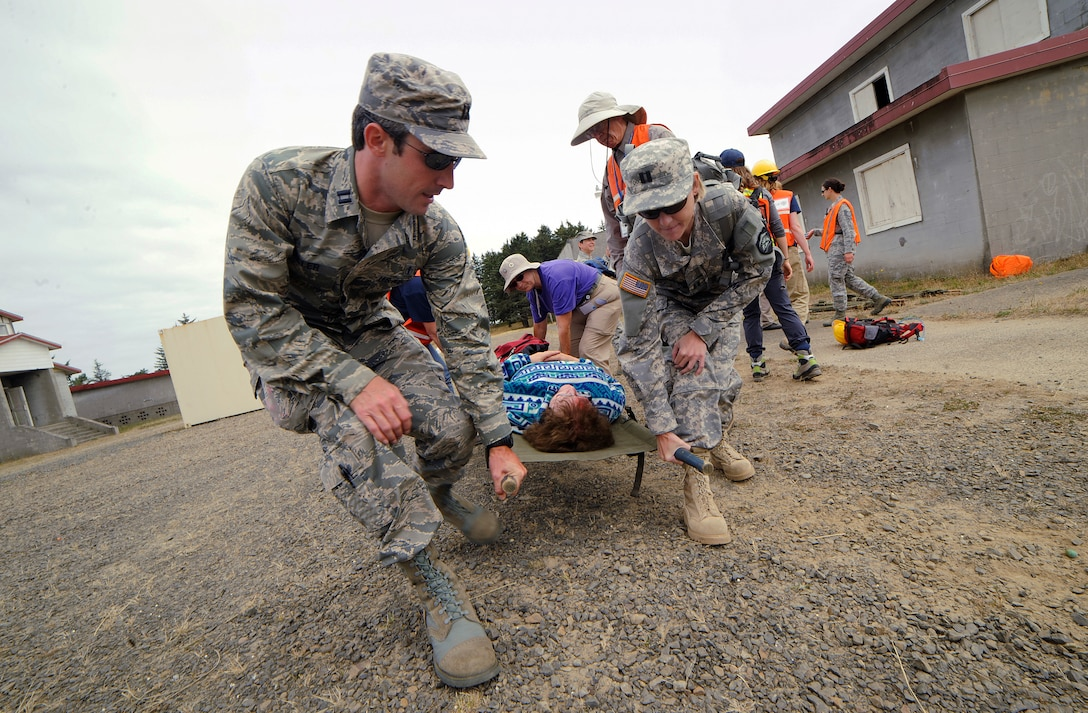 Capt. Jonathon Miller, with the 124th Fighter Wing Medical Group, Idaho Air National Guard, left, and Oregon Army National Guard Capt. Amy Kerfoot, right, lift a simulated casualty during Pathfinder-Minutemen Exercise Aug. 5, 2015 at Camp Rilea in Warrenton, Oregon. The event is a joint multi-agency, multi-state disaster preparedness exercise based on response to a possible Cascadia Subduction Zone event. Officials believe the Northwest is overdue for a magnitude 7.0 or greater earthquake. (U.S. Air National Guard photo by Tech. Sgt. John Hughel, 142nd Fighter Wing Public Affairs/Released)