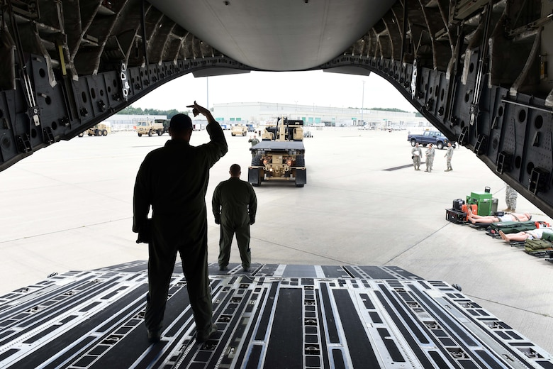 Airmen from the 89th Airlift Squadron direct a forklift during joint multi-unit C-17 Globemaster III deployment training exercises June 6, 2016 at the 180th Fighter Wing in Swanton, Ohio. The exercises provided training on the proper handling and placement capabilities of deployable assets to Airmen of all ranks.  (Air National Guard photo by SSgt Shane Hughes/Released)