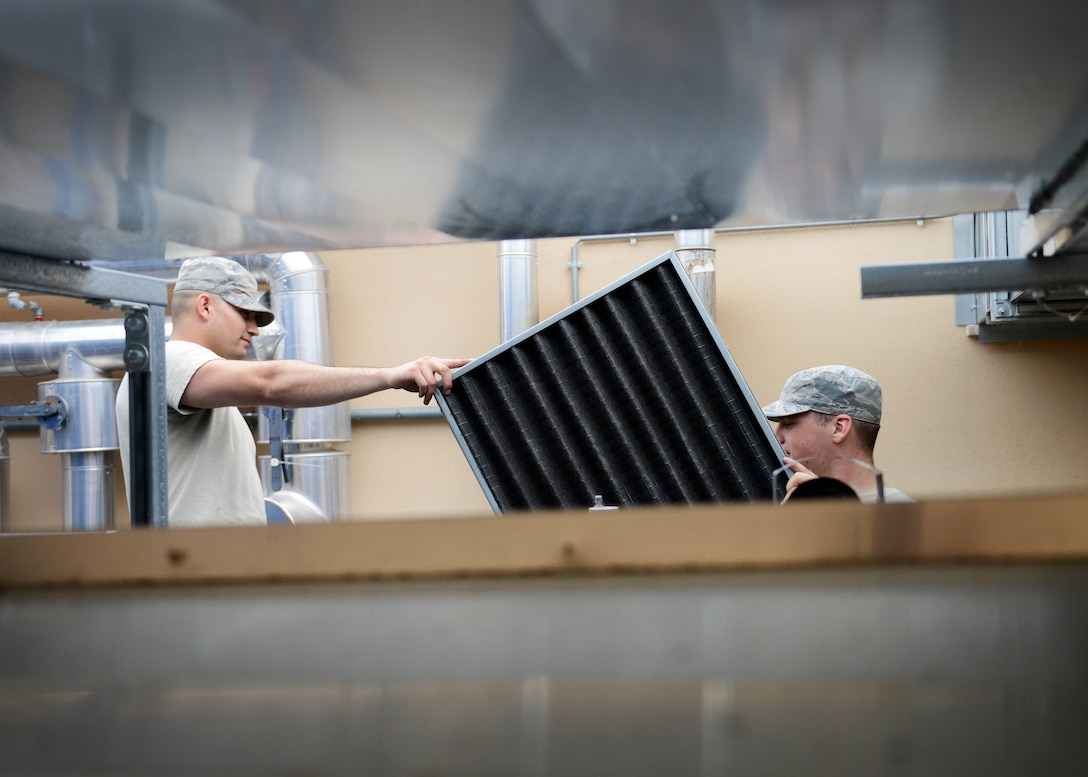 U.S. Air Force Airmen 1st Class Aaron Ohlemacher and Jedadiah Floyd, 31st Civil Engineer Squadron heating, ventilation, air conditioning and refrigeration technician, cleans an air filter, July 29, 2015, at Aviano Air Base, Italy. HVAC Technicians clean air filters every quarter, ensuring all machine parts are properly working. (U.S. Air Force photo by Airman 1st Class Deana Heitzman/Released)