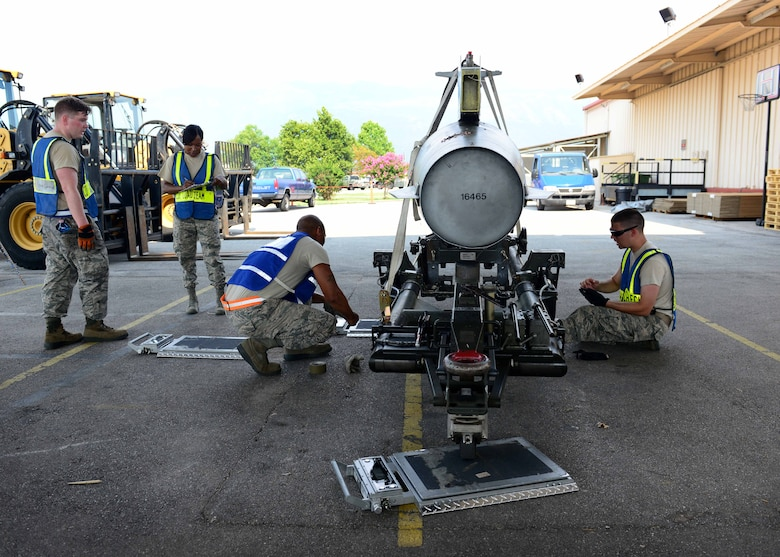 Airmen from the 31st Logistics Readiness Squadron cargo deployment function measure and weigh an excess fuel tank prior to a deployment Aug. 8, 2015, at Aviano Air Base, Italy. This deployment coincides with Turkey's decision to host U.S. aircraft to conduct counter-ISIL operations. (U.S. Air Force photo by Airman 1st Class Deana Heitzman)