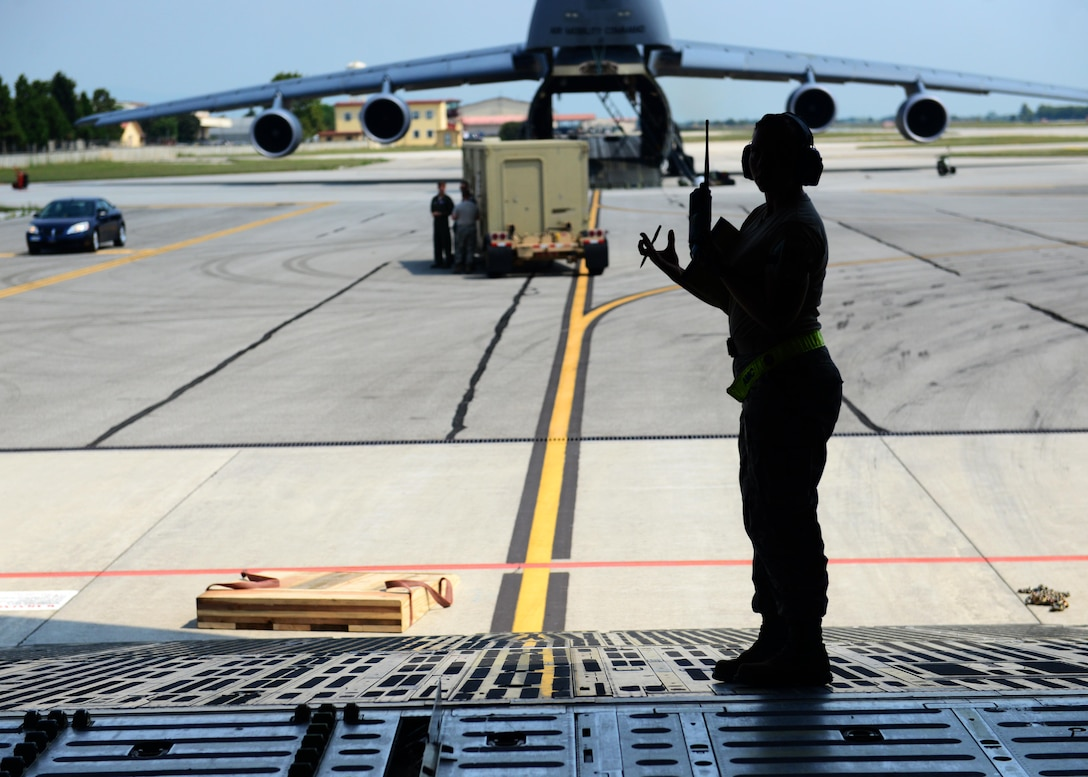 An Airman from the 724th Air Mobility Squadron oversees cargo loading procedures on a C-5 Super Galaxy delivering cargo in support of Operation Inherent Resolve Aug. 8, 2015, at Aviano Air Base, Italy. This deployment coincides with Turkey's decision to host U.S. aircraft to conduct counter-ISIL operations. (U.S. Air Force photo by Airman 1st Class Deana Heitzman)