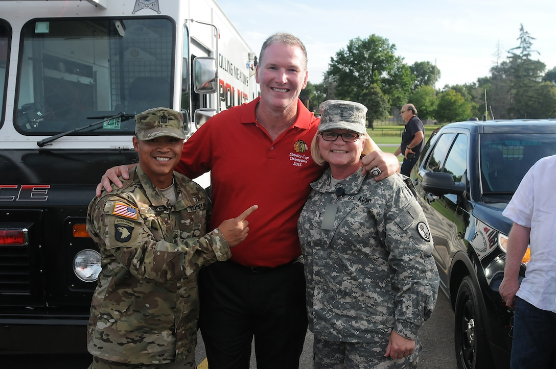 Army Reserve 1st. Sgt. Dominic Baruelo, left, and Chief Warrant Officer 2 Sabine Irby, right, both assigned to the 327th MP BN, 200th Military Police Command, pause for a photo with Chicago Blackhawks' national anthem singer, Jim Cornelison center, at the Rolling Meadows Police Department National Night Out community event, Aug. 4. Soldiers from the 85th Support Command also participated in the three-hour event here and simultaneously at the Village of Arlington Heights National Night Out event. (U.S. Army photo by Spc. David Lietz/Released)