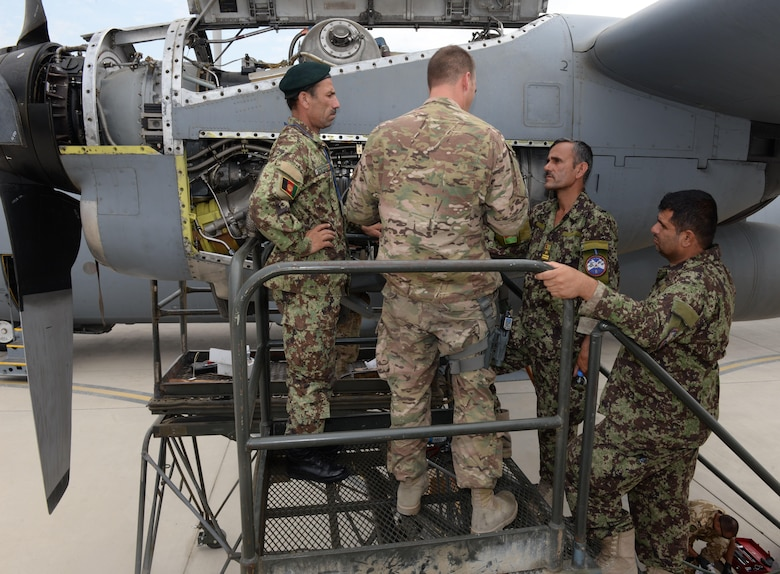 Master Sgt. Antonio Policicchio, 440th Air Expeditionary Advisory Squadron C-130 engine mechanic, discusses the engine bleed air system and changing the speed sensitive valve filter with Afghan air force mechanics July 28, 2015, at Hamid Karzai International Airport.  Policicchio is deployed to Kabul, Afghanistan, from the 911th Maintenance Squadron in Pittsburgh, Pennsylvania. He is part of the Train, Advise, Assist Command-Air (TAAC-Air) unit that works shoulder-to-shoulder with Afghan partners to develop a professional, capable, and sustainable Air Force. (U.S. Air Force photo by Senior Airman Cierra Presentado)