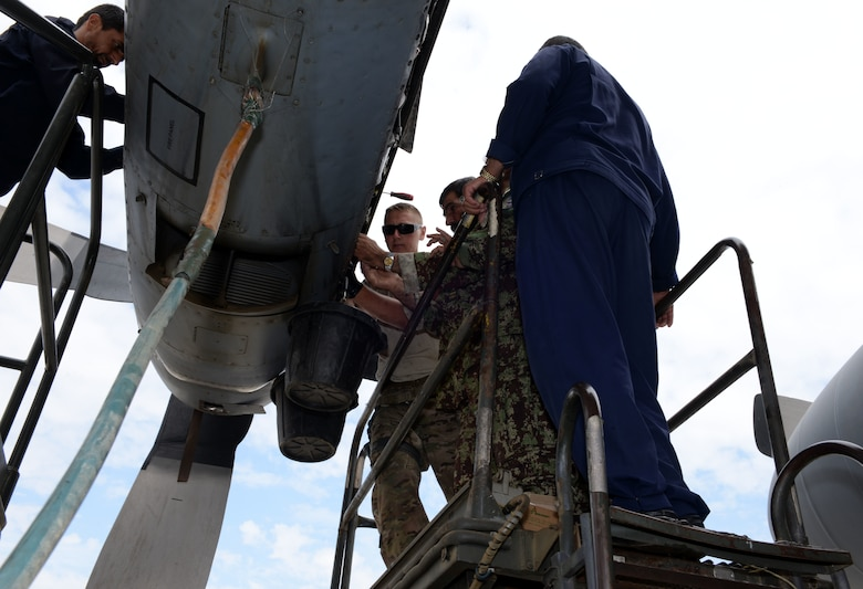 Staff Sgt. Nathanial Weitzell, 440th Air Expeditionary Advisory Squadron C-130 engine mechanic, replaces the external scavenge oil filter with Afghan air force mechanics July 28, 2015, at Hamid Karzai International Airport.  Weitzell is deployed to Kabul, Afghanistan, from the 911th Maintenance Squadron in Pittsburgh, Pennsylvania.  He is part of the Train, Advise, Assist Command-Air (TAAC-Air) unit that works shoulder-to-shoulder with Afghan partners to develop a professional, capable, and sustainable Air Force.  (U.S. Air Force photo by Senior Airman Cierra Presentado)